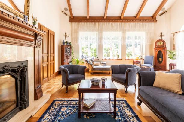 dunklen holztisch auf teppich zwischen blauen sessel und sofa im luxuriösen interieur mit kamin. echtes foto - teppich englisch stock-fotos und bilder