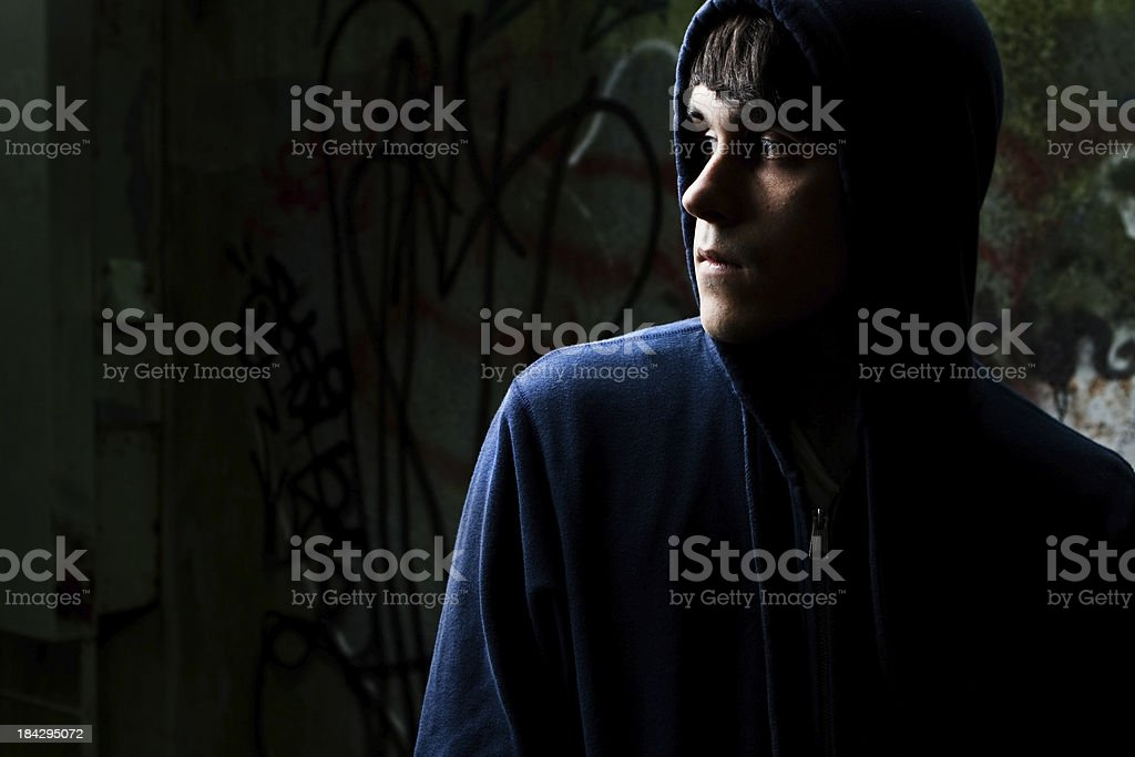 Dark young man wearing hooded sweatshirt stock photo