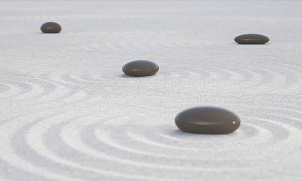 Dunkle Zen Steinen auf einem breiten Sandstrand – Foto