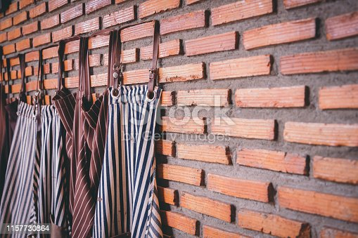 istock Dark-colored aprons hung together with bricks on the wall in the cafe. Portrait of a set of aprons hung on the wall, arranged in a mess, ready to allow customers to join the newly opened coffee shop. 1157730864