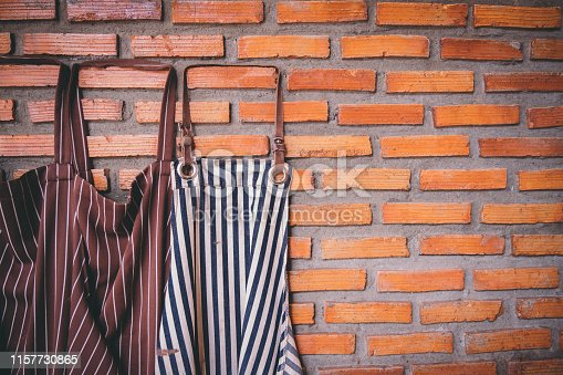 istock Dark-colored aprons hung together with bricks on the wall in the cafe. Portrait of a set of aprons hung on the wall, arranged in a mess, ready to allow customers to join the newly opened coffee shop. 1157730865
