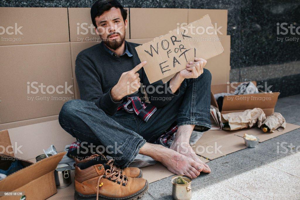 Cabelos escuros e barbado de mendigo é sentado e apontando no pedaço de papelão que diz trabalhar para comer. Ele não tem um emprego. Sommebody de furos de homem irá ajudá-lo a encontrar um emprego - Foto de stock de Adulto royalty-free