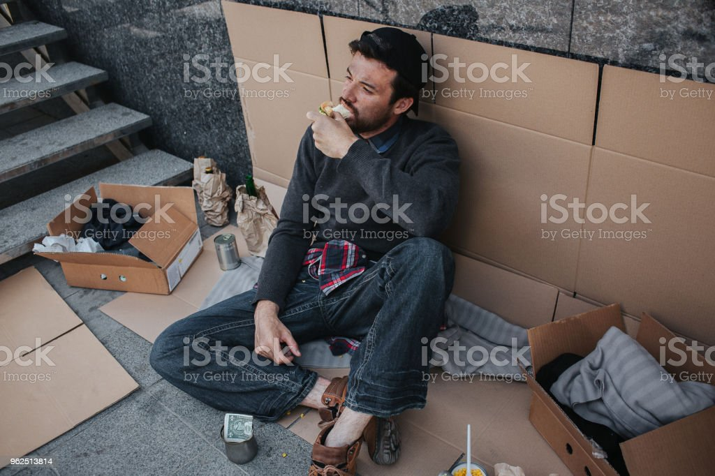Dark-haired and dirty man is sitting on cardboard and eating sandwich. His pose is relaxed. Guy is looking up. There is a lot of stuff that surrounds him - Royalty-free Adult Stock Photo