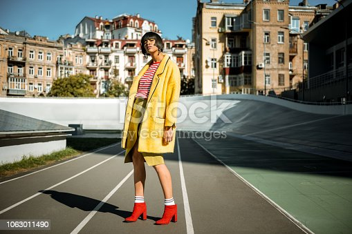 Displaying fashion tendencies. Dark-haired attractive woman posturing on the running track in bright yellow fluffy cloak