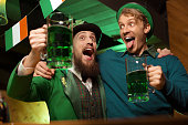 Dark-haired bearded young man in a leprechaun hat and his friend looking drunk