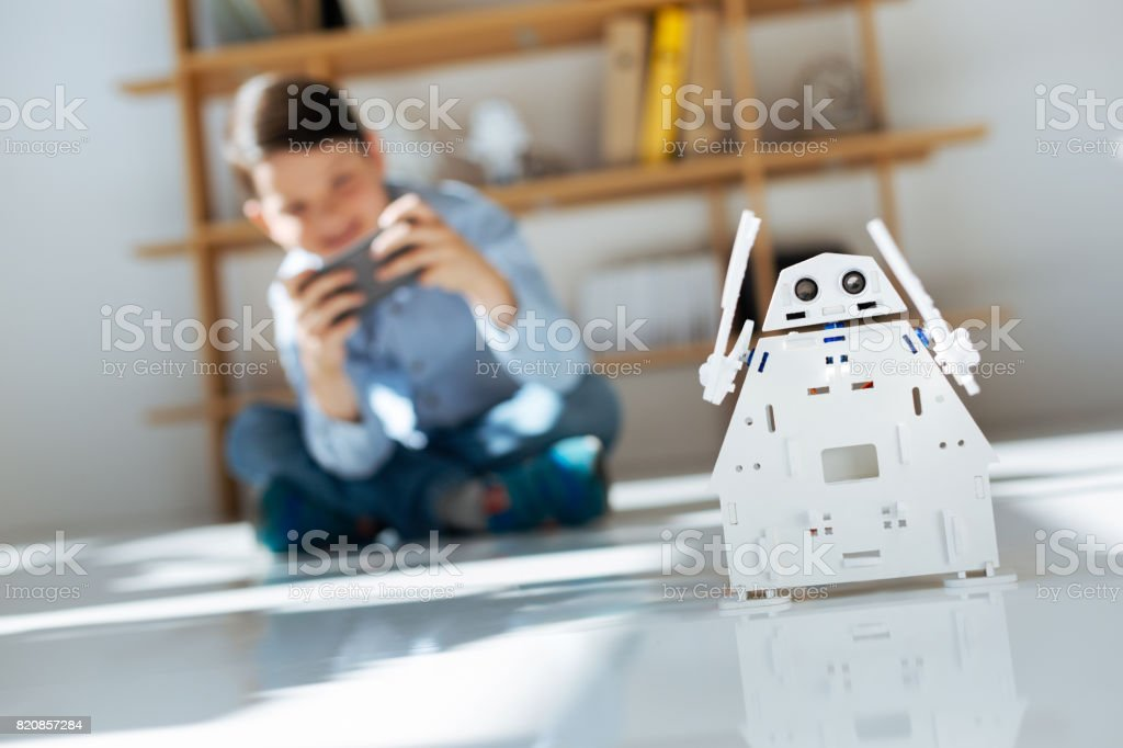 Dark-haired little boy controlling his white robot stock photo