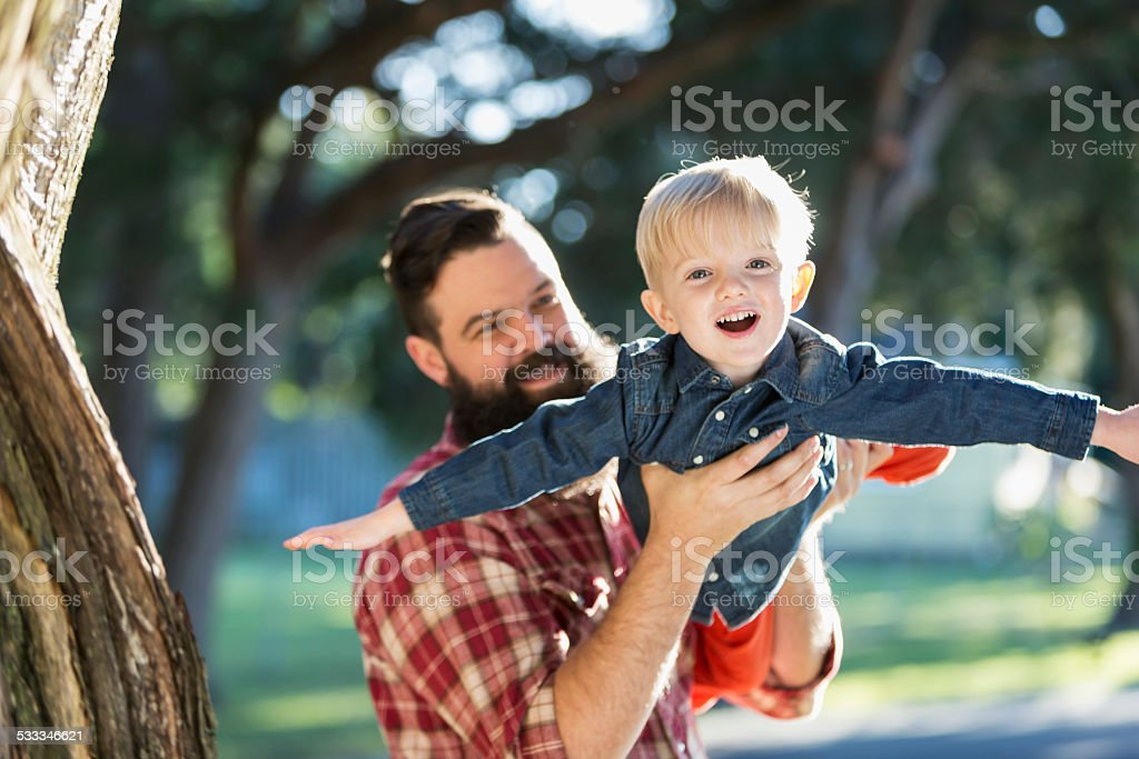 Dark-haired man with blond playful son stock photo