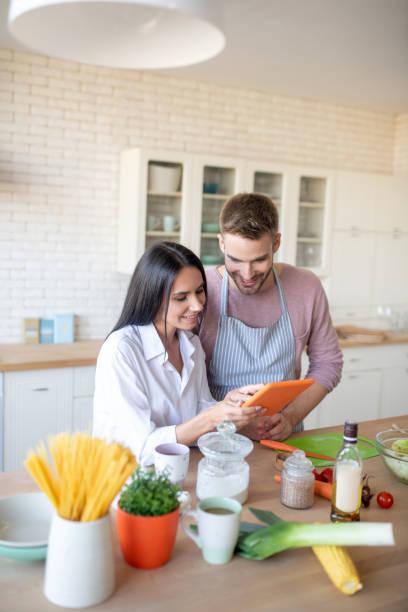 Dunkelhaarige Frau zeigt ihrem Mann kulinarischerezepte – Foto