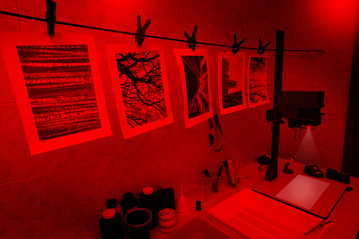 Darkroom with printing tools and materials for analog photography, illuminated by a red light. Photo enlarger projecting light, easel, focusing magnifier, enlarger timer and negative carrier. Tanks filled with chemicals and various tools fill the table. Bottles with developer bath, stop bath and fixer. On the foreground some black and white photographs hanging on a wire, waiting for complete drying. Some piece of negative film are visible on the background. All pictures on paper constitute personal work.