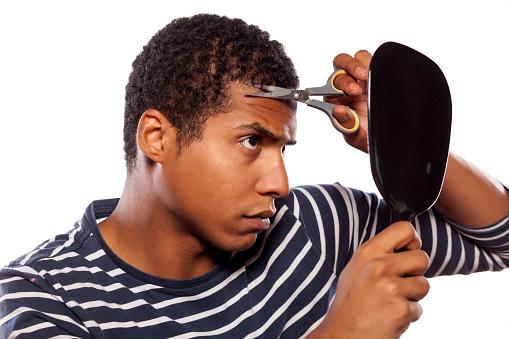 istock Dark-skinned boy haircut himself with scissors 531694355