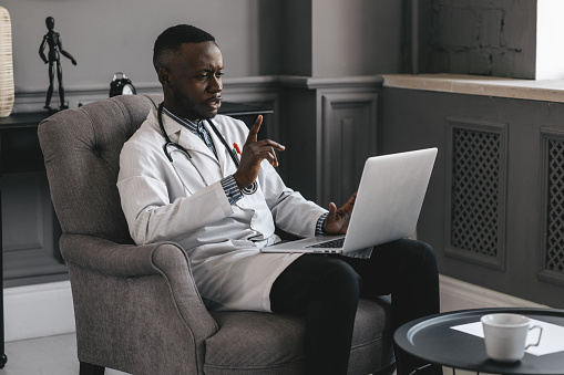 dark-skinned doctor talking on skype zoom with laptop waving
