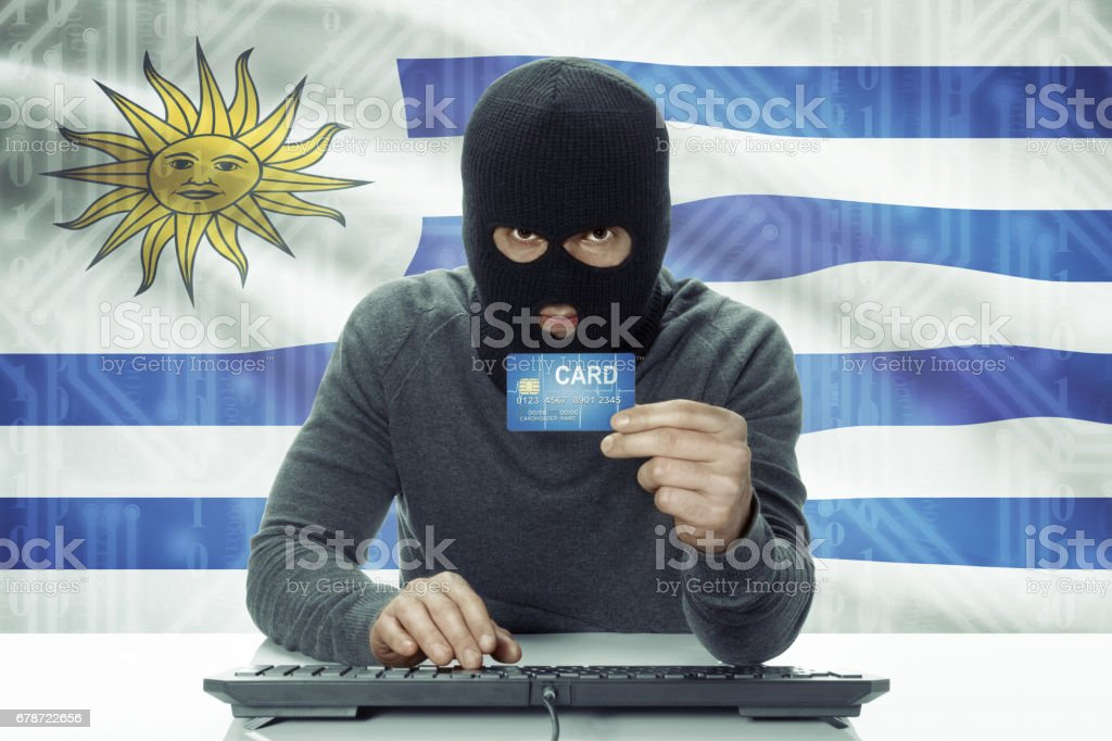 Dark-skinned hacker with flag on background holding credit card - Uruguay photo libre de droits