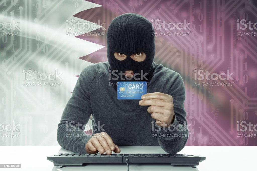 Dark-skinned hacker with flag on background holding credit card - Qatar royalty-free stock photo