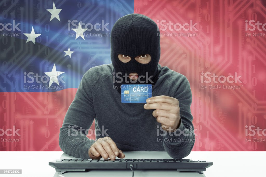 Dark-skinned hacker with flag on background holding credit card - Samoa photo libre de droits