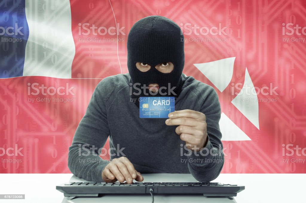 Dark-skinned hacker with flag on background holding credit card - Wallis and Futuna photo libre de droits