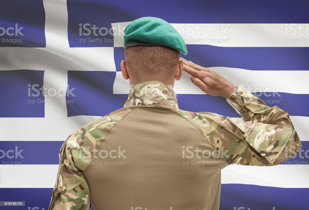 Dark-skinned soldier with flag on background - Greece photo libre de droits