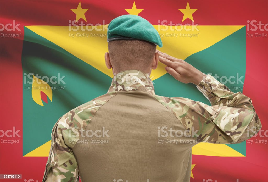 Dark-skinned soldier with flag on background - Grenada photo libre de droits