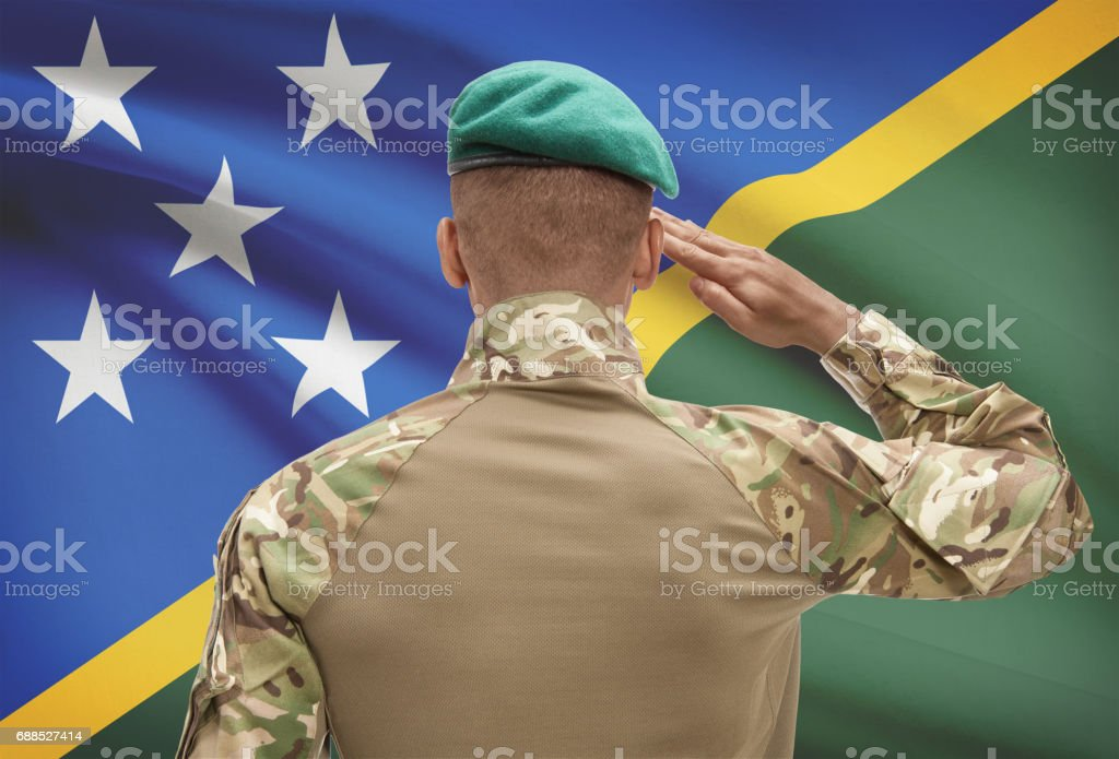 Dark-skinned soldier with flag on background - Solomon Islands stock photo