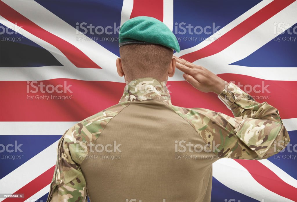 Dark-skinned soldier with flag on background - United Kingdom stock photo