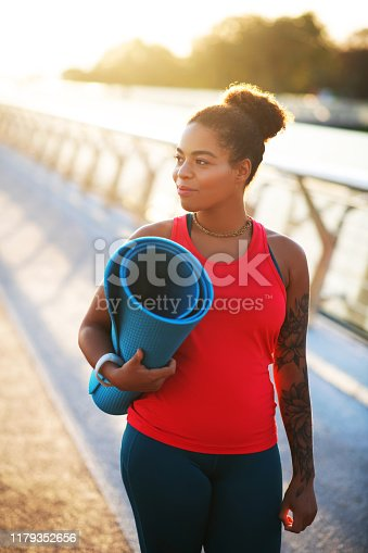 Woman walking. Dark-skinned young woman walking to workout with sport mat in the morning