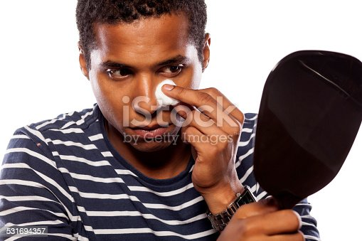 istock Dark-skinned young man cleans his face with cotton pad 531694357