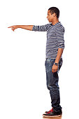 istock Dark-skinned young man in jeans showing a direction 531643915