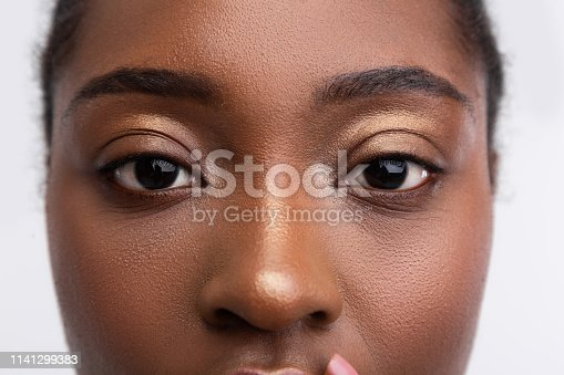 Golden eyeshades. Close up of young dark-skinned woman with nice golden eyeshades