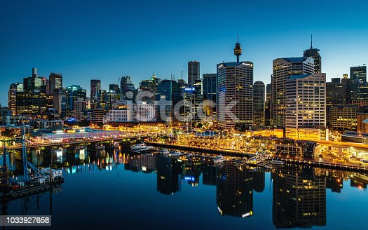Beautiful illuminated modern Skyscraper Cityscape of Darling Harbour reflecting in the harbor. Shot from above. Darling Harbor, Sydney, New South Wales, Australia.