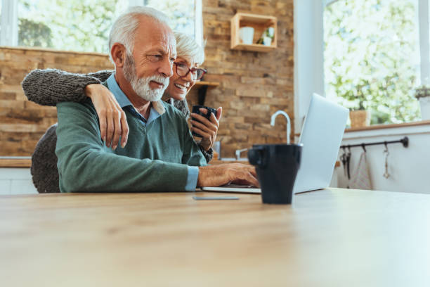 Darling, look what I found on internet Mature couple using their laptop mature couple stock pictures, royalty-free photos & images