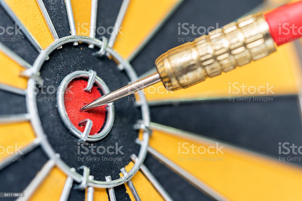 dart arrow hitting in target bullseye of dartboard stock photo