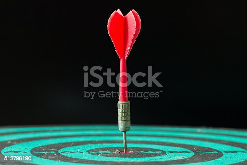 istock Dart arrow hitting in the center of green dartboard. 513796190