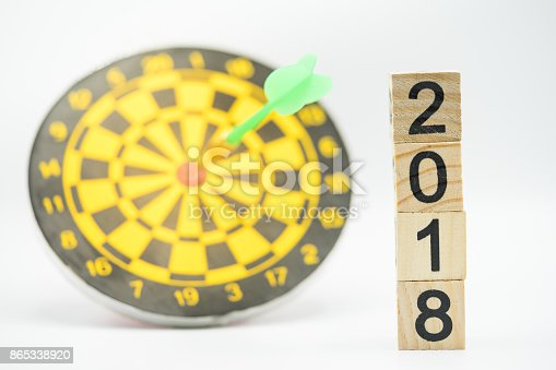 istock Dart arrow hitting in the target center of dartboard and wooden text icon 2018 with white background. Target business, achieve and victory concept. 865338920