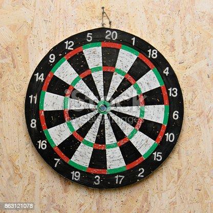 istock Dart arrow hitting in the target center of dartboard 863121078
