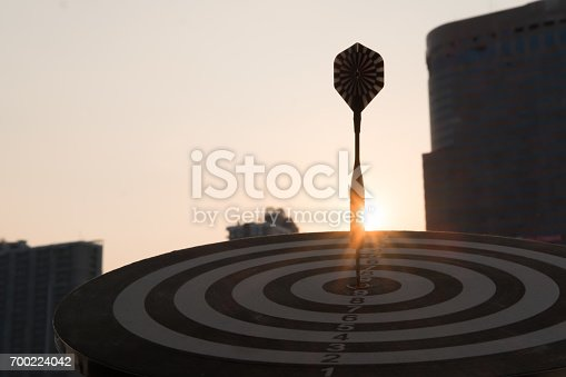 istock Dart arrow hitting in the target center of dartboard with modern city and sunset background. Target business, achieve and victory concept. 700224042