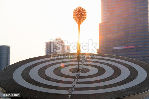 istock Dart arrow hitting in the target center of dartboard with modern city and sunset background. Target business, achieve and victory concept. 700224102