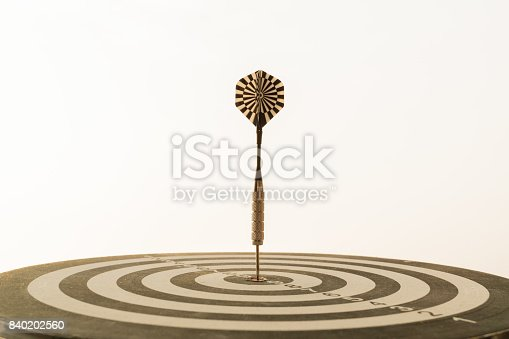 istock Dart arrow hitting in the target center of dartboard with modern city and sunset background. Target business, achieve and victory concept . 840202560