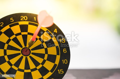 istock Dart arrow hitting in the target center of dartboard with modern city and sunset background. Target business, achieve and victory concept. 843362230