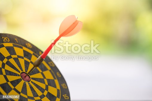 istock Dart arrow hitting in the target center of dartboard with modern city and sunset background. Target business, achieve and victory concept. 843363382