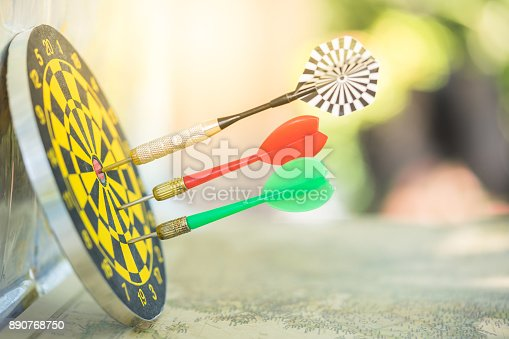 istock Dart arrow hitting in the target center of dartboard with modern city and sunset background. Target business, achieve and victory concept. 890768750