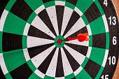 istock Dart arrow in bullseye target on dartboard 1021031302