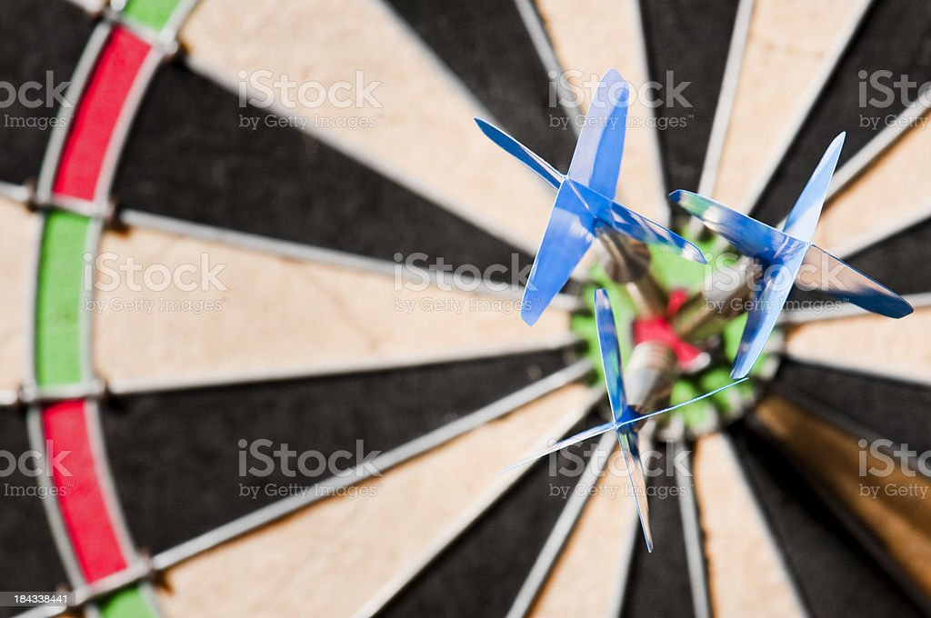 Dart board with three darts in bulls eye at centre royalty-free stock photo