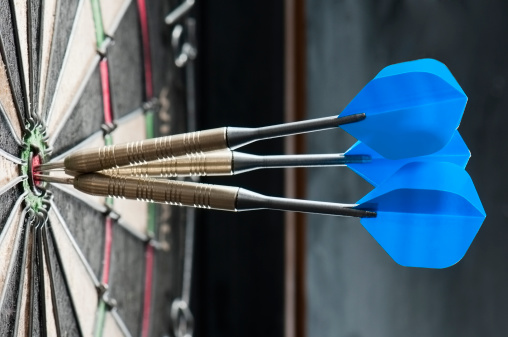 Dart board with three darts in the bulls eye