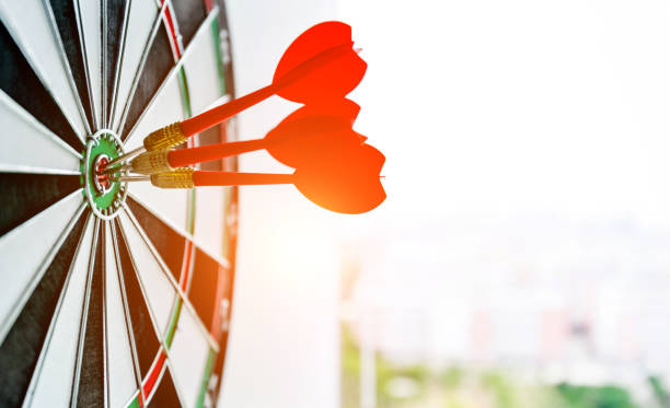 dart board with three darts outdoors - goal stock photos and pictures