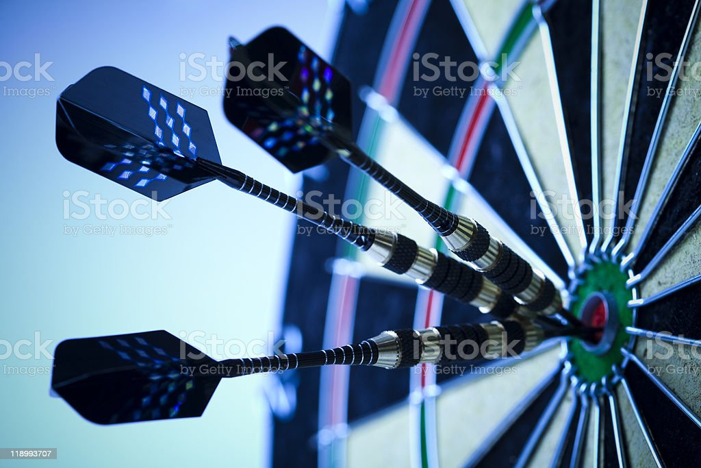 A dart board with three darts precisely in the bulls eye stock photo
