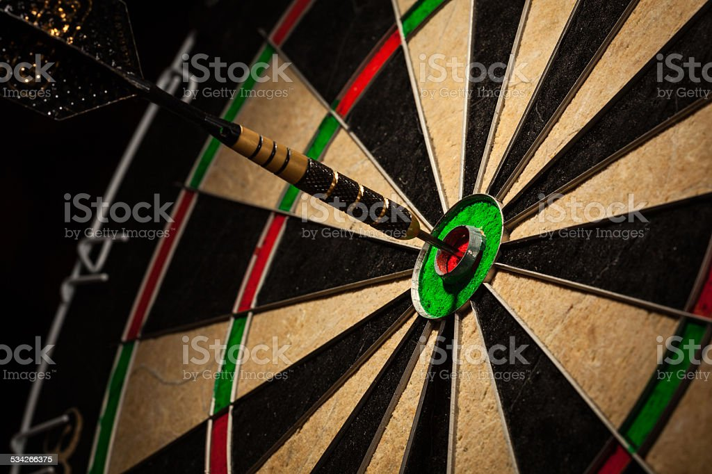 Dart in bull's eye close up stock photo