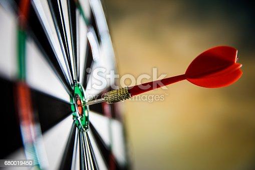 886643538 istock photo Dart in center of target 680019450