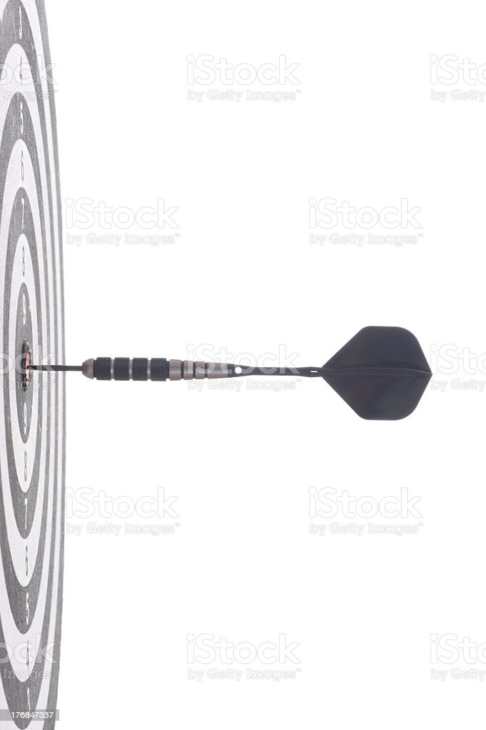 A dart in the bulls eye of a dart board, seen from the side stock photo