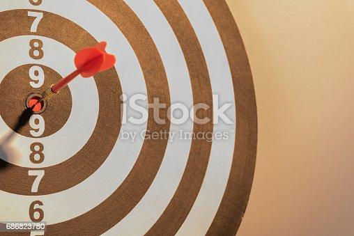 istock Dart target arrow hitting on bullseye with sun light 686823780