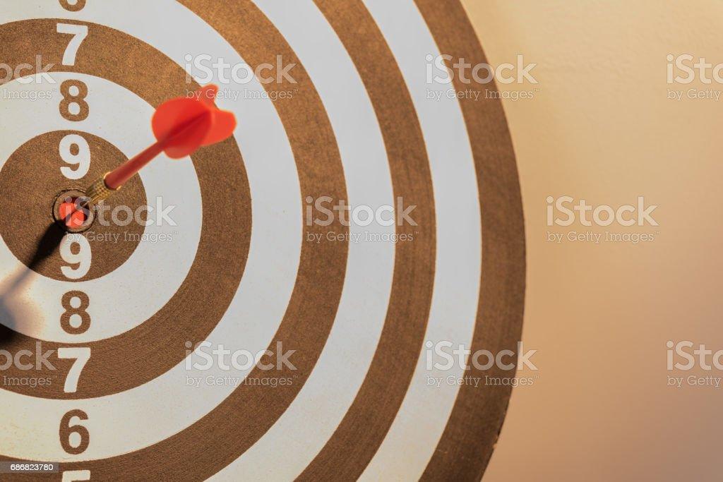 Dart target arrow hitting on bullseye with sun light stock photo