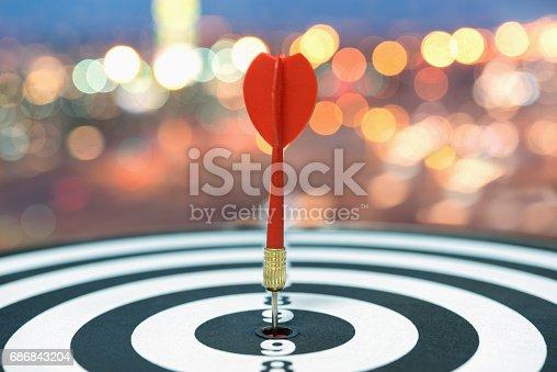 istock Dart target arrow on bullseye over blurred bokeh background 686843204